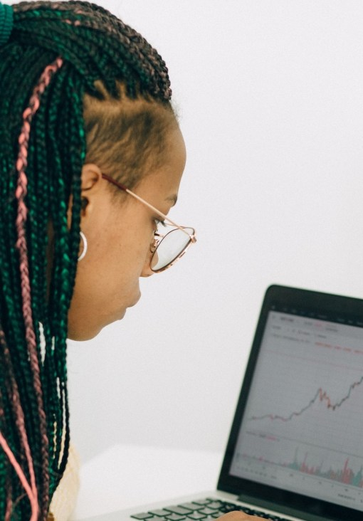 woman looking at her stocks and shares on a laptop