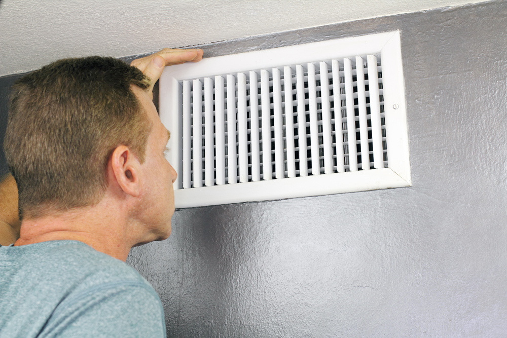 man inspecting air duct to see if it needs cleaning