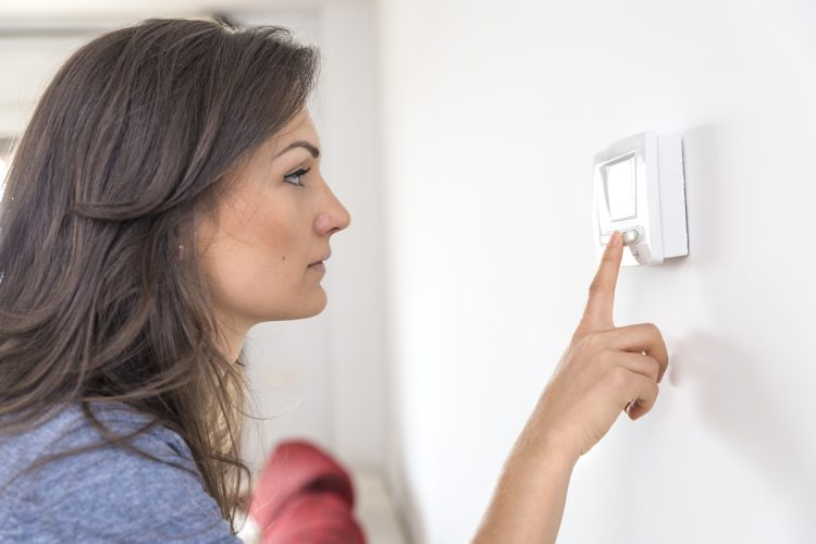Woman programming thermostat