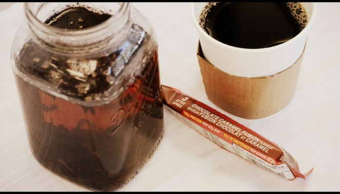 Tea in mason jar, energy bar, and cup of coffee