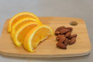 Orange slices and almonds on chopping board