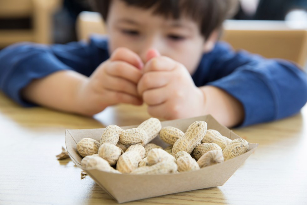 boy opening up peanuts to eat in a restaurant
