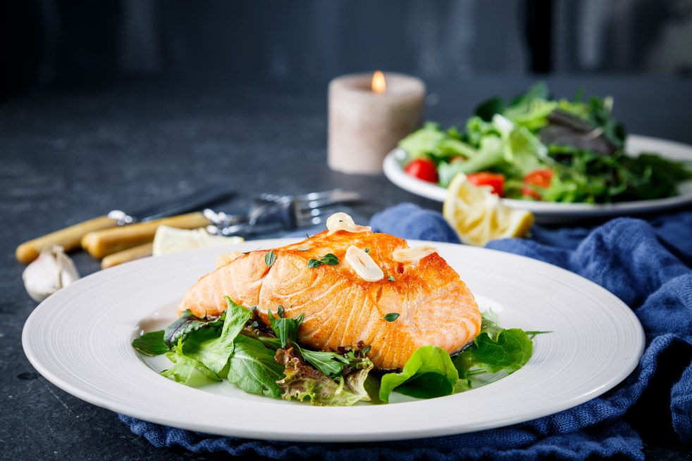 Salad topped with Salmon fish on white plate