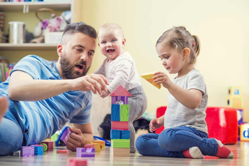 Dad playing blocks with his daughters