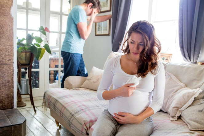 Pregnant individual sitting on couch crying. Partner in background with hand on his forehead.