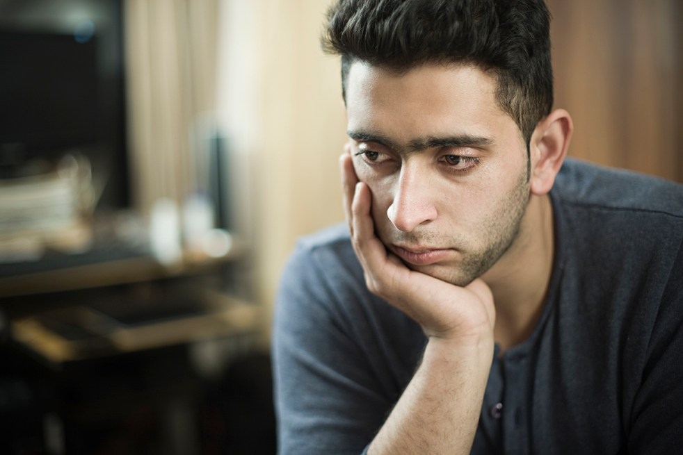 young man thinking by resting his head on hand and looking away with and blank expression
