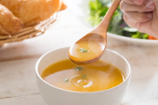 Pumpkin soup in white bowl with wooden spoon