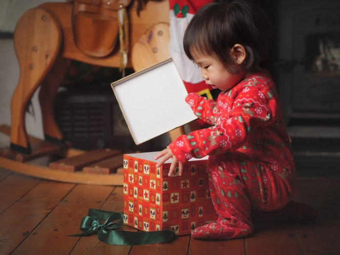 Toddler opening gift in red box