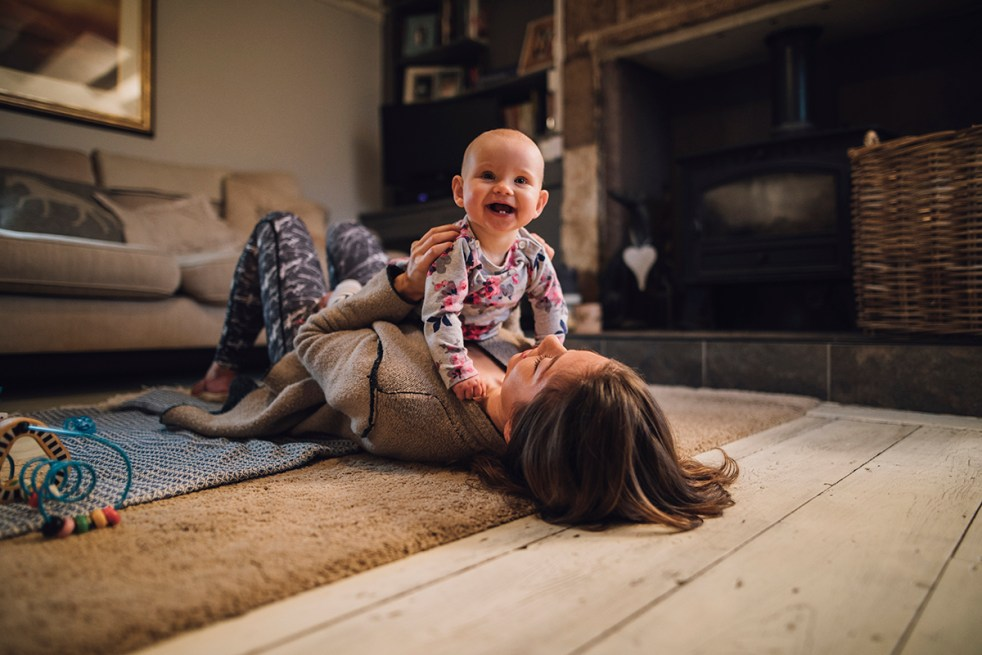 Baby laughing while parent holds baby on chest while lying on floor