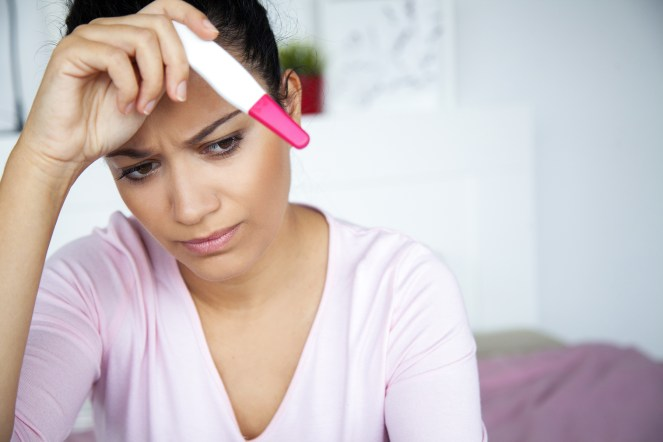 worried individual with pregnancy test