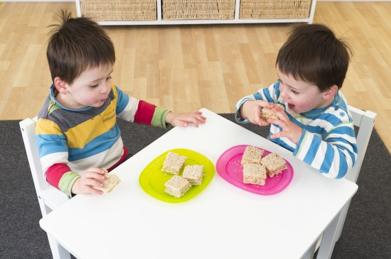two kids sitting at a white square table eating small sandwiches