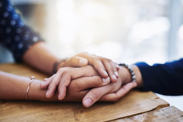 Closeup shot of two people holding hands in comfort