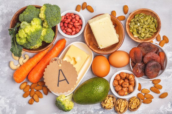 Assortment of high vitamin A sources. Carrots, nuts, broccoli, butter, cheese, avocado, apricots, seeds, eggs.