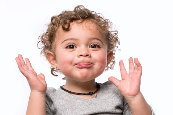 Toddler smiling with hands up near face.
