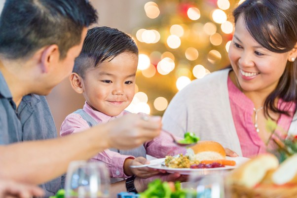 A family having dinner during the holidays. Parent is putting food on his child's plate