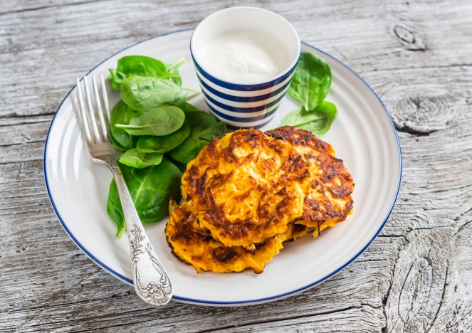Sweet potato carrot pancakes and fresh spinach on a light wooden background