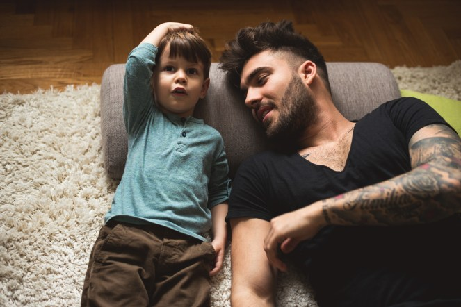 Parent and son laying on the floor talking