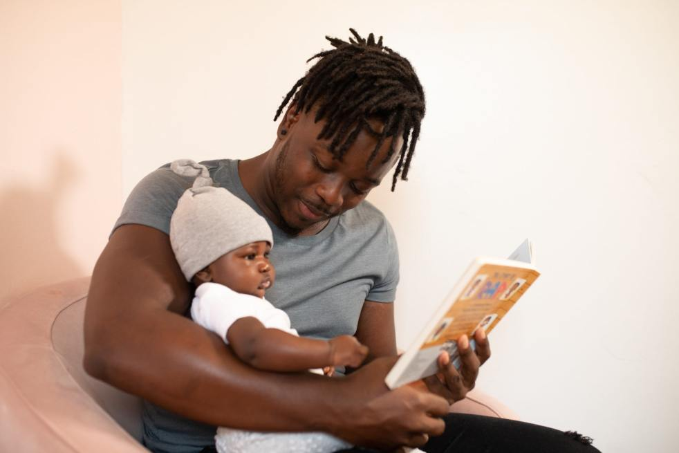Infant sitting in parent's arms while parent is reading a book to baby