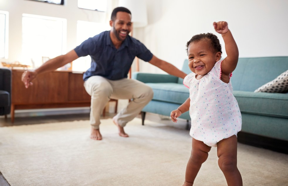 Toddler and parent dancing in living room