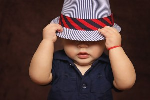 baby wearing hat covering eyes