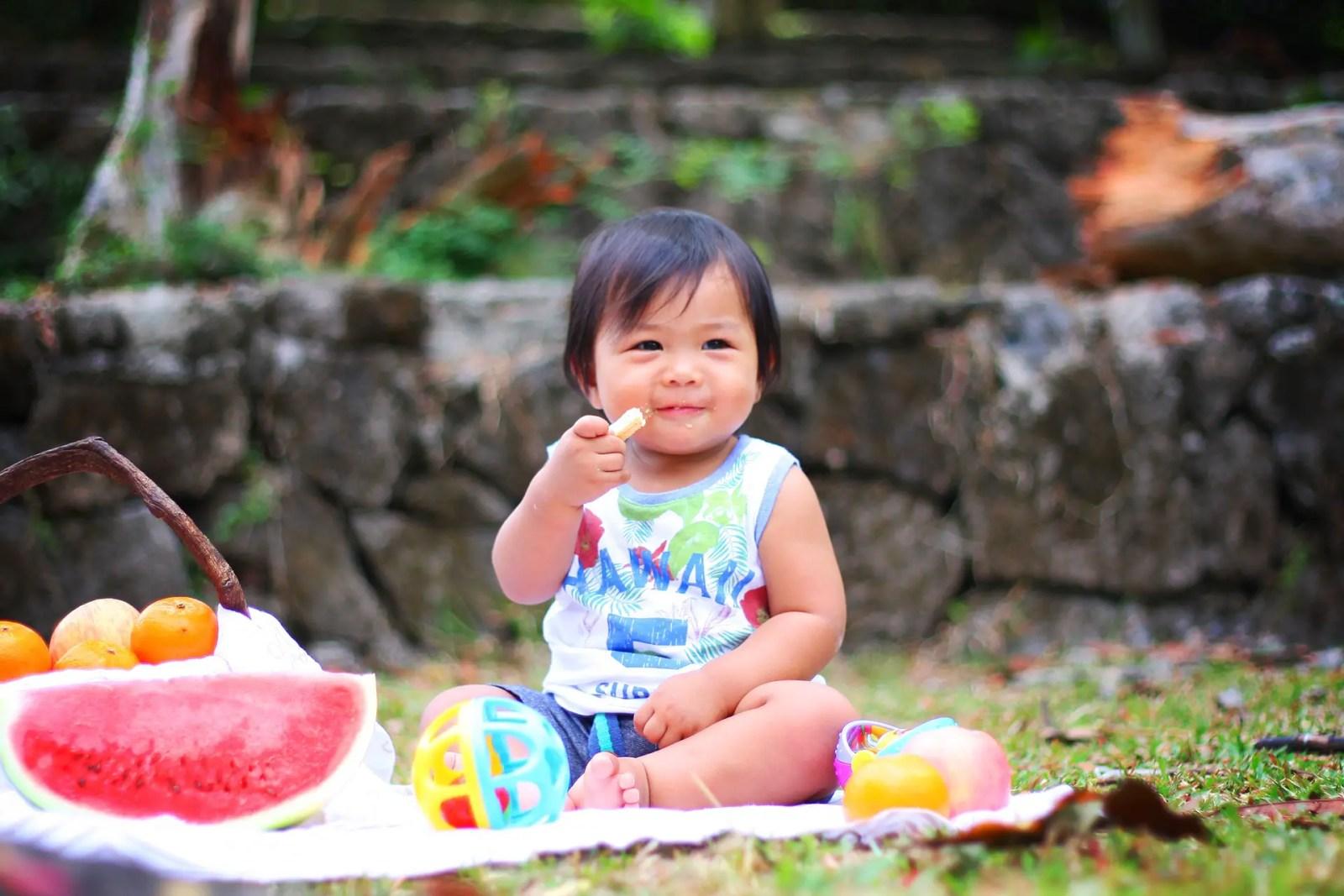 Bebé comiendo frutas en el parque