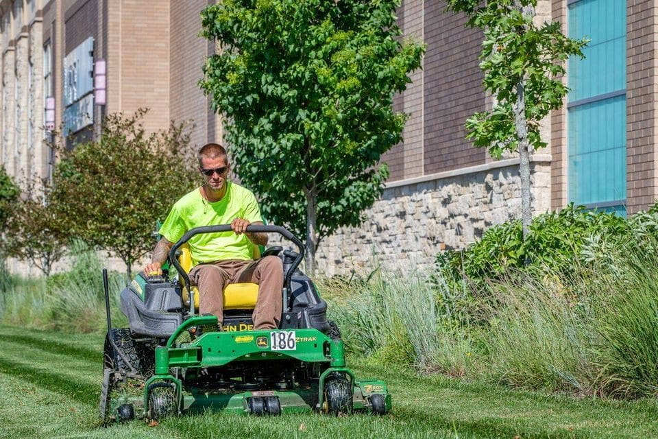 Employee of Premier Lawn and Landscape mowing grass on a zero-turn mower at a commercial site in Ottawa, Ontario