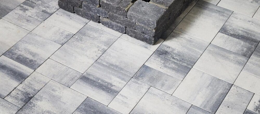 Grey interlock pavers with a raised fireplace.