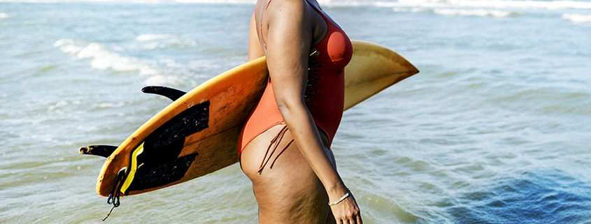 woman with liposuction carrying surfboard
