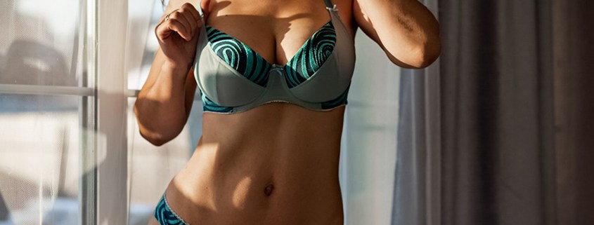 woman with breast augmentation in green lingerie