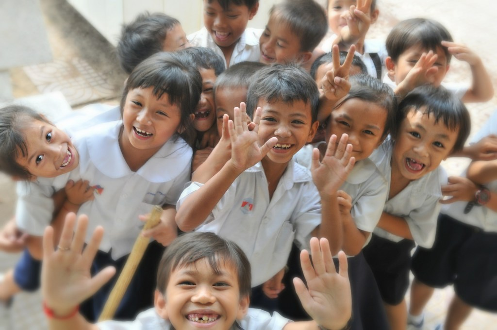 A bunch of children waving at the camera.