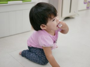 baby on the floor putting a piece of plastic in her mouth