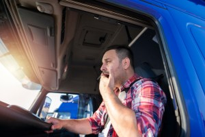 Truck driver yawning while driving.