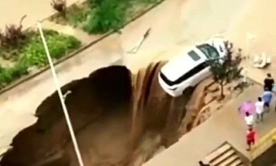 Dramatic moment some Chinese men pulled a car to safety as it dangles at the edge of a sinkhole