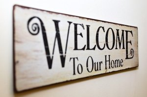 "A wooden sign that says ""Welcome to our home"""""