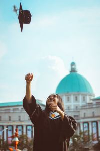 Girl throwing her graduation hat up in the air