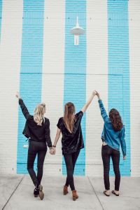 Image of three friends standing in front of a blue-white wall