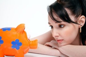girl looking at a piggy bank