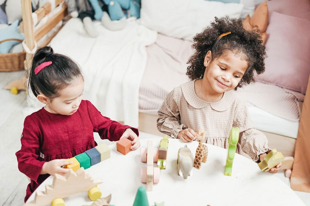Picture of two kids sitting at a table playing with blocks and toys smiling