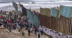 Migrants from caravan seen climbing border fence; no troops