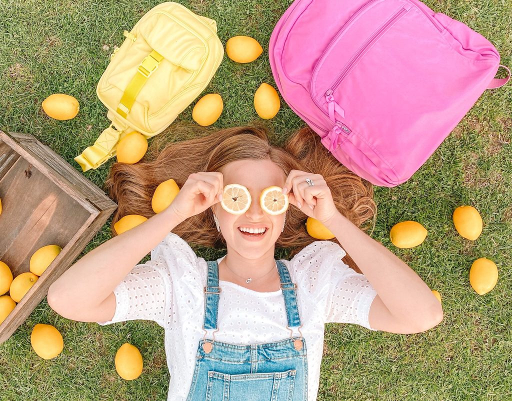 girl lays with vera bradley recycled cotton bags in the grass with lemons