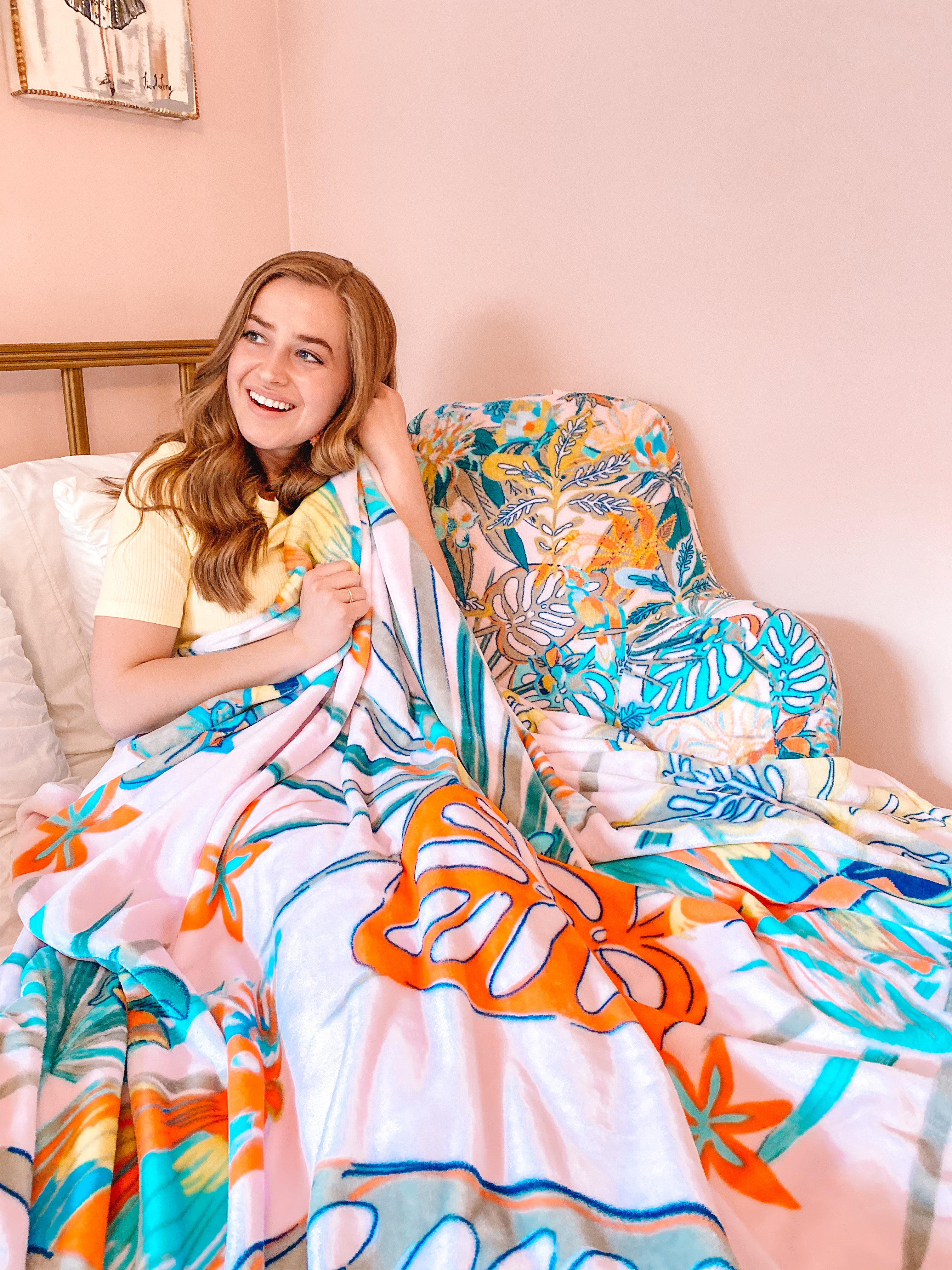 woman sits in pink bedroom with soft vera bradley blanket in pattern rain forest canopy