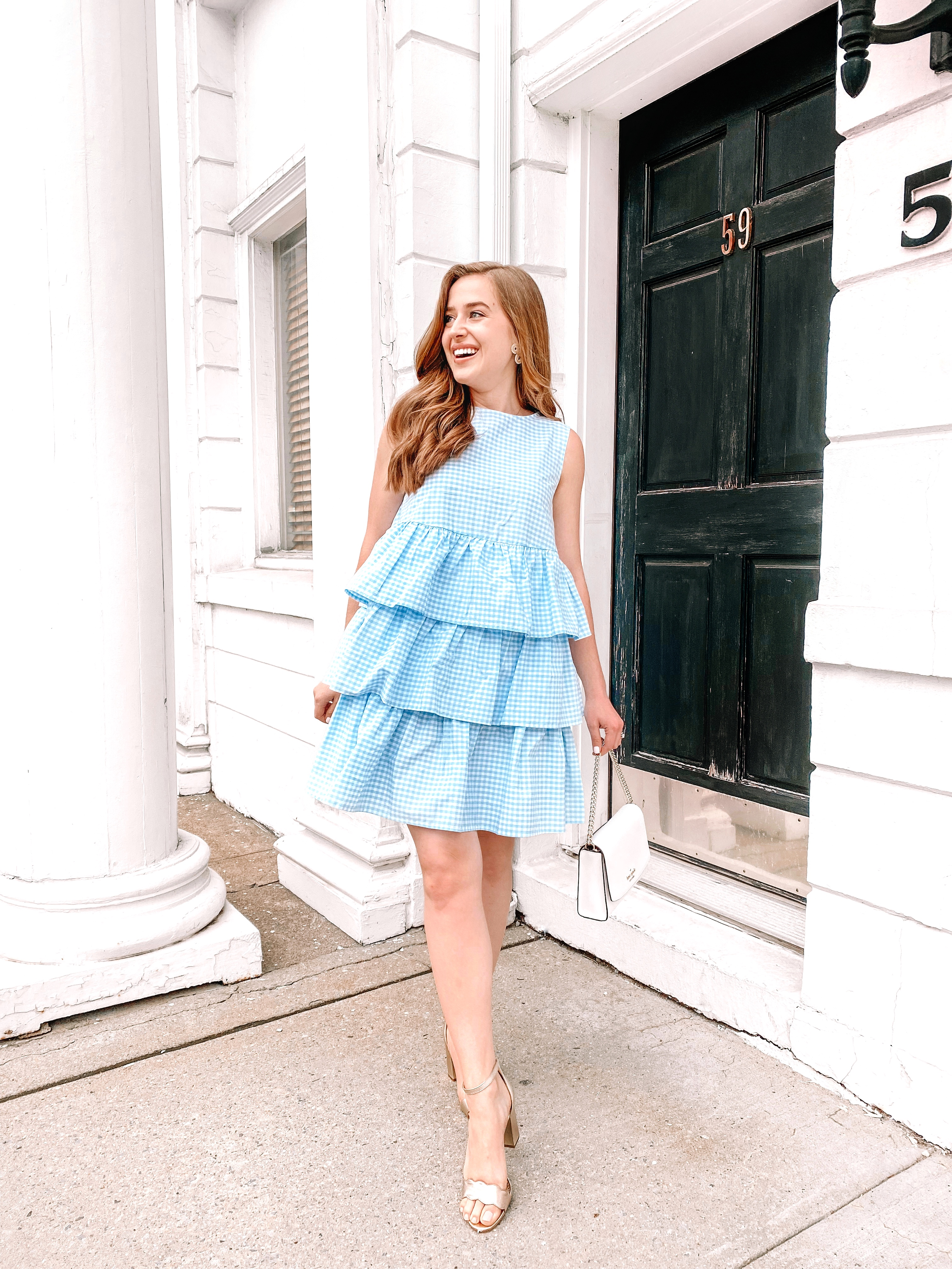 woman smiles in a blue gingham spring dress by a white building and black door