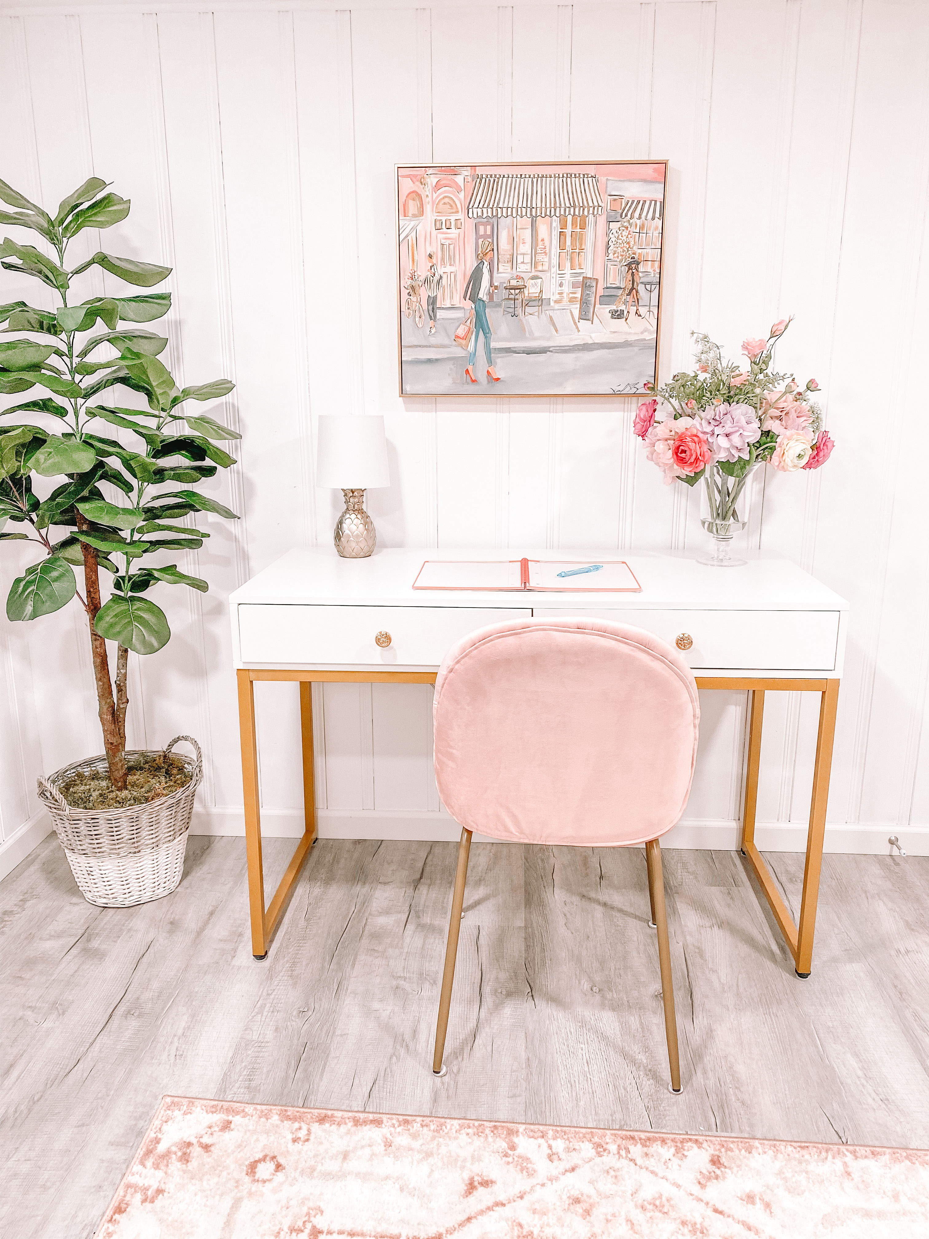 fake potted tree next to white desk and pink chair in home office