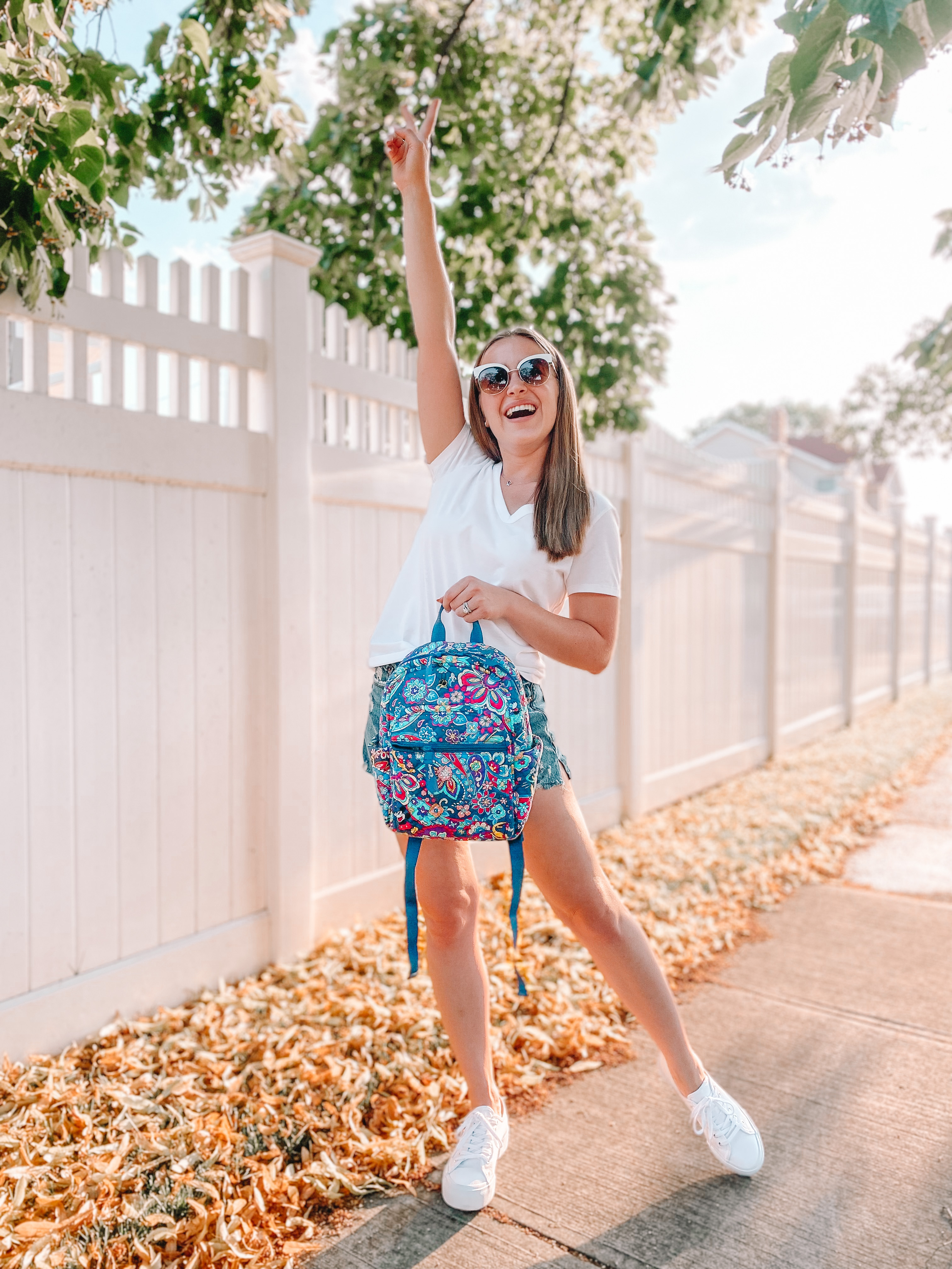 girl holds up peace sign while holding her vera bradley x disney backpack from excitement of a disney vacation