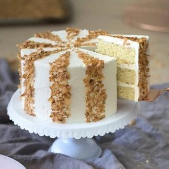 Light and Dreamy Coconut Cake   Preppy Kitchen photo showing a striped coconut cake on a white cake stand