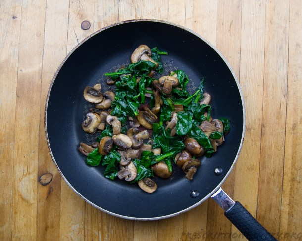 Sautéed spinach and mushrooms in pan
