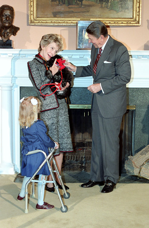 The Reagans hold Lucky the puppy as Kristen Ellis looks on in the Roosevelt Room, Dec. 21, 1984. Photo courtesy Reagan Libary.