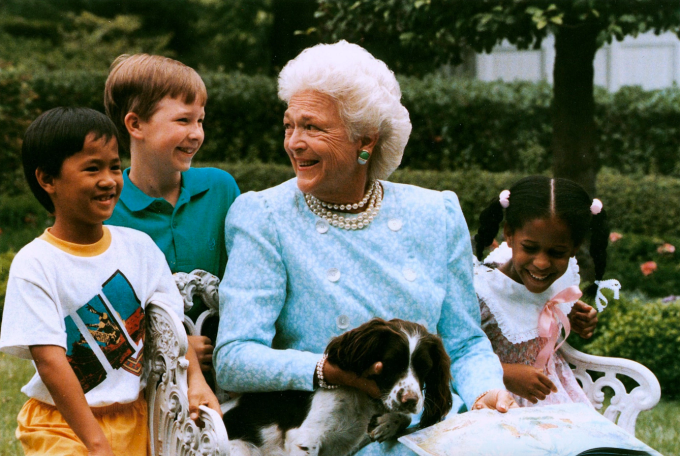 President George H.W. Bush's dog Millie, a springer spaniel, was the first presidential pet to write a book. In this photo, First Lady Barbara Bush reads a story to children with Millie.