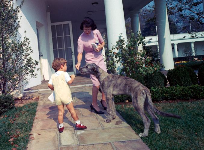 Little John F. Kennedy, Jr. and Evelyn Lincoln, the president's personal secretary, stand with Wolf outside the Oval Office, Oct. 24, 1963.