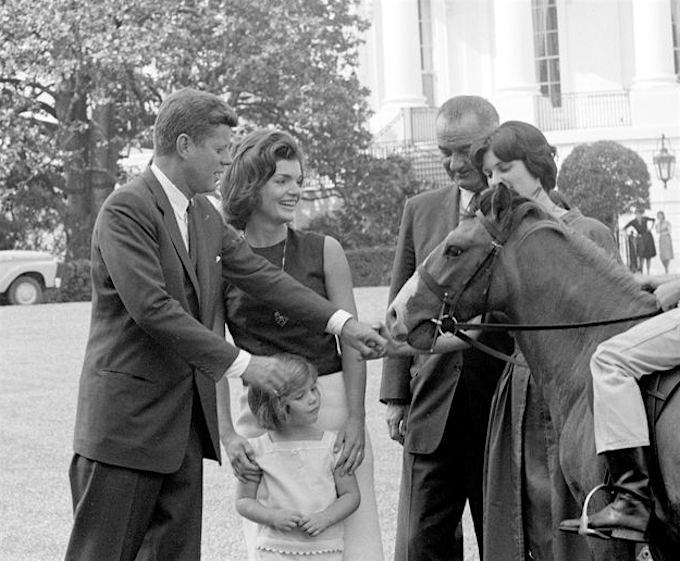President John F. Kennedy, First Lady Jackie Kennedy, and their daughter, Caroline, visit with Vice President Lyndon B. Johnson and his daughter Lynda Bird Johnson, May 17, 1962. Also pictured is Tex, a pony given to Caroline as a gift from Johnson.